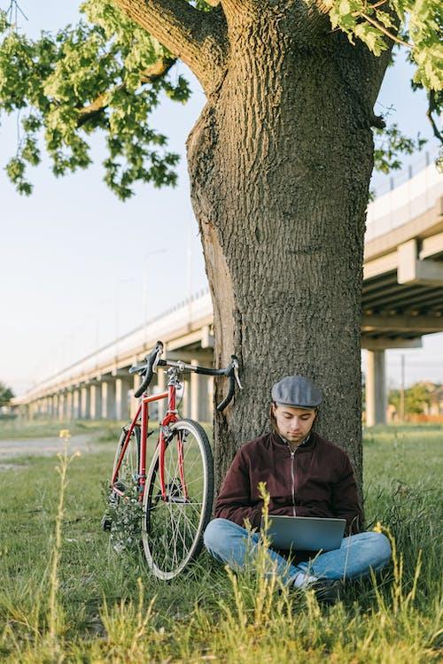 Man in Black Jacket Sitting on Blue Bicycle Beside Brown Tree