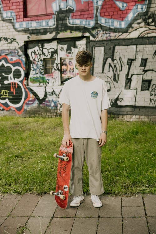 Boy in White Crew Neck T-shirt and Gray Pants Standing on Green Grass Field during