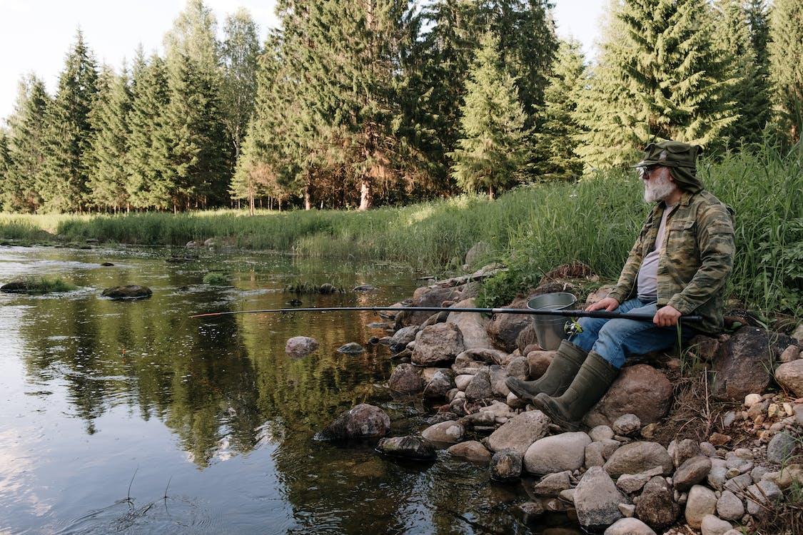 Man in Blue Jacket Sitting on Rock Beside River