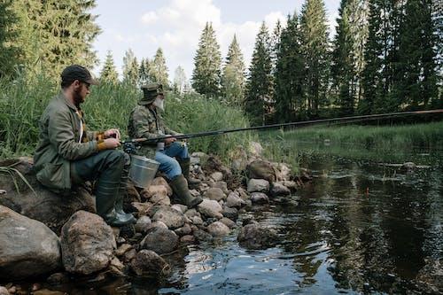 Man in Green Jacket Holding Fishing Rod Sitting on Rock Beside River