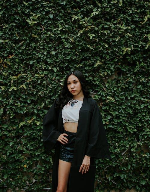 Stylish woman standing near green shrubs