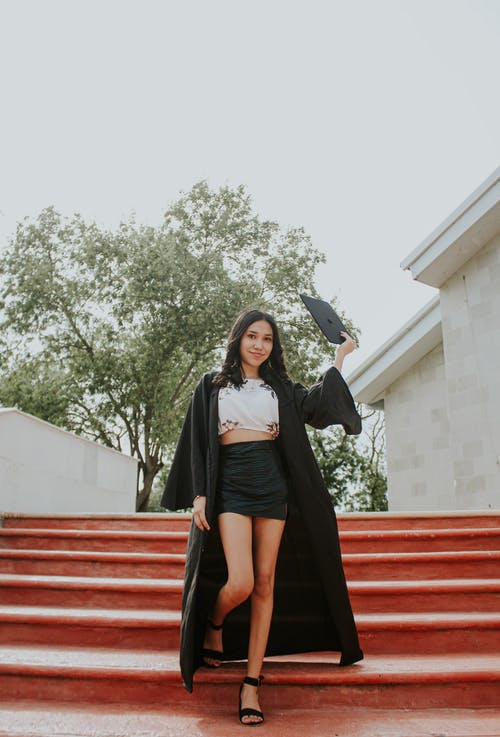 Full body of elegant woman in graduation outfit standing on stairs and holding classic black hat