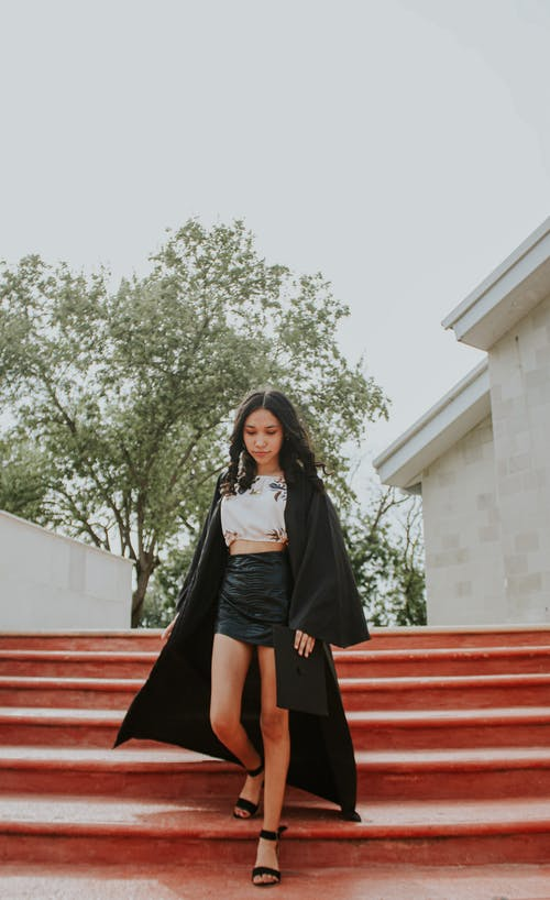 Stylish young woman standing on stairs