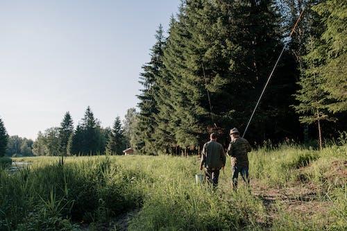 2 Men Walking on Green Grass Field