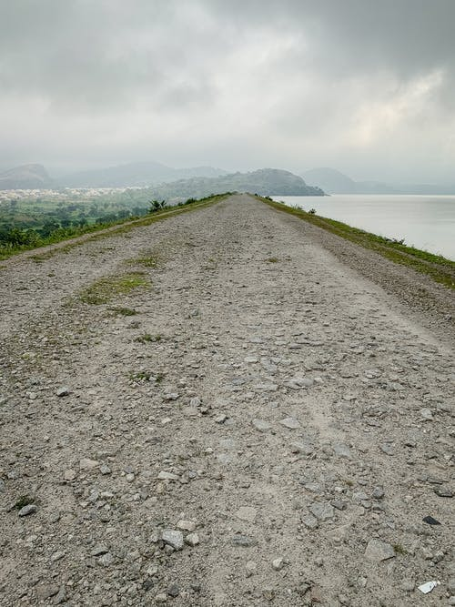 Gray Dirt Road Near Green Grass Field and Body of Water