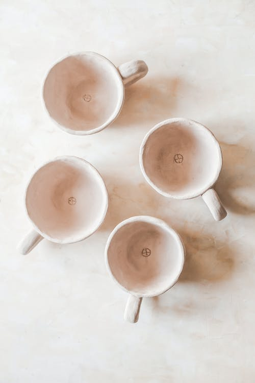 Top view of empty beige ceramic cups placed on light table in light space