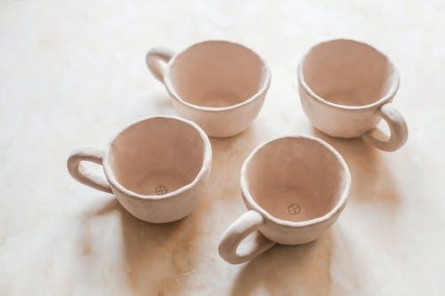 Handmade ceramic cups on light surface