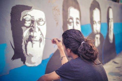 Unrecognizable man painting graffiti on wall