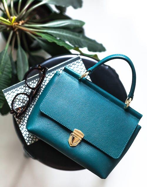 Top view trendy elegant dark blue handbag placed on stool near copybook and eyeglasses in light room