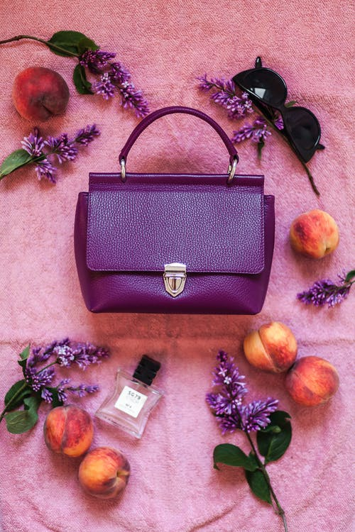 Top view composition of trendy violet handbag arranged on pink cloth amidst ripe peaches perfume bottle and stylish eyeglasses