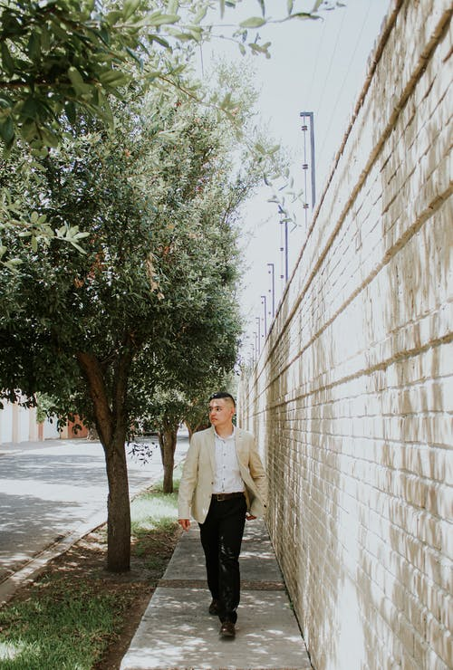 Full body of stylish ethnic male in elegant outfit walking on paved road near tall brick wall