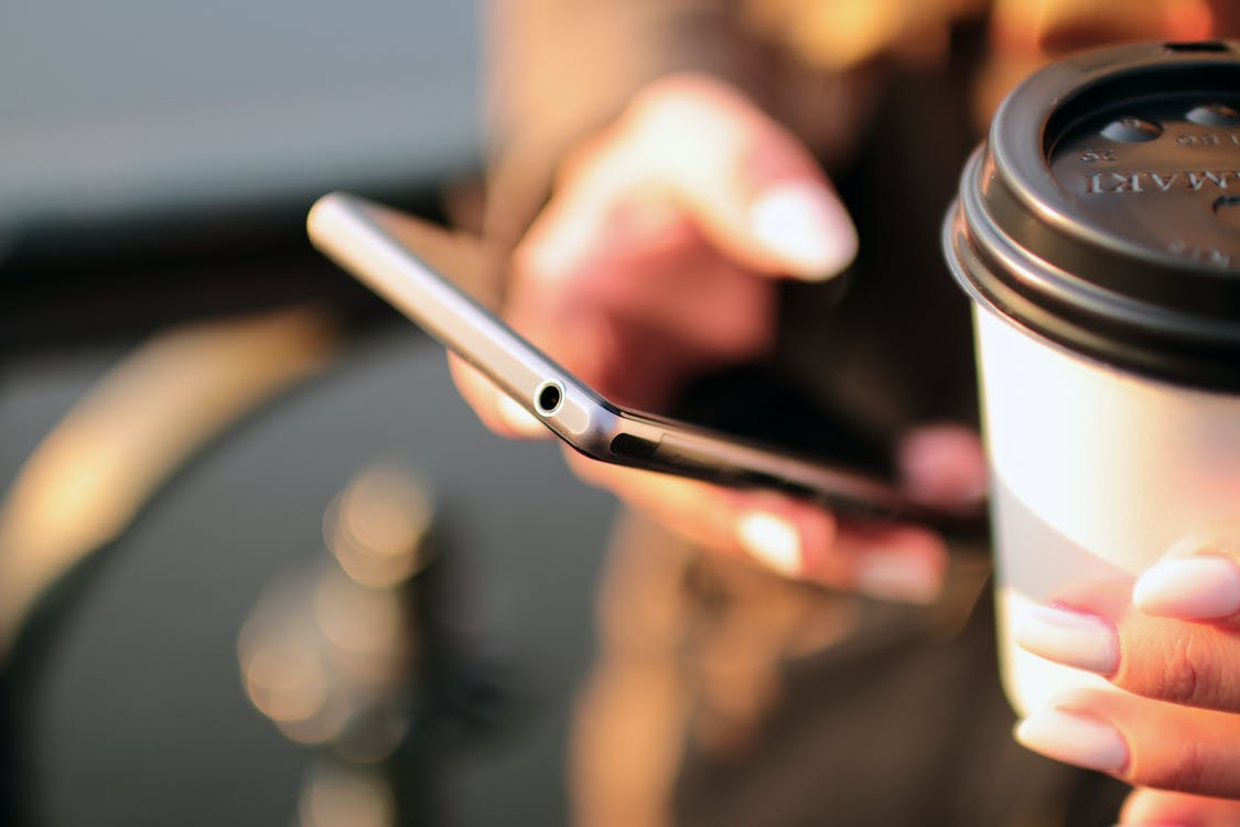 Close up of a woman using her smartphone in one hand while holding a coffee in the other.