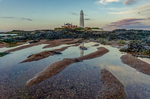 White Lighthouse on Brown Sand Under Blue Sky