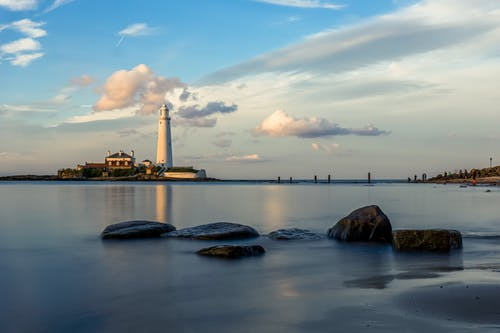 White Lighthouse on Rock Formation on Sea Under Blue and White Cloudy Sky