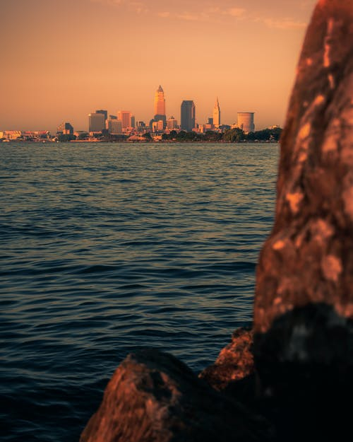 Picturesque view of calm ocean rippling near rock against sunset sky with skyscrapers in distance in evening time in coastal city
