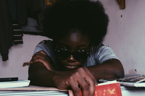 Black woman in sunglasses lying on hands and looking at camera