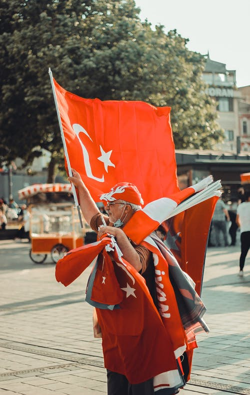 Man in Red and White Traditional Dress Holding Red Flag