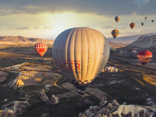 From above of colorful air balloons flying over mountain ridge in sunlight against cloudy sky in nature in summer evening