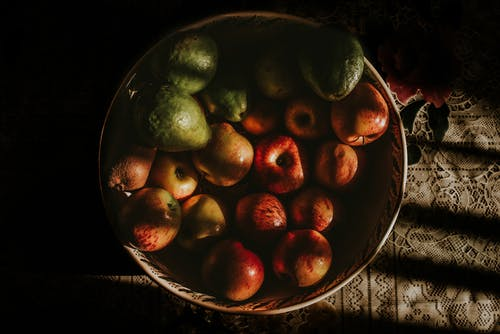 Green and Red Round Fruits on Stainless Steel Bowl