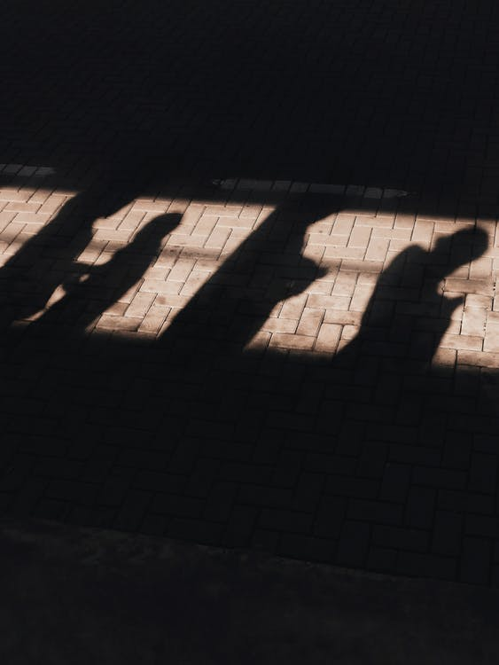 Shadows of people on concrete tile on street