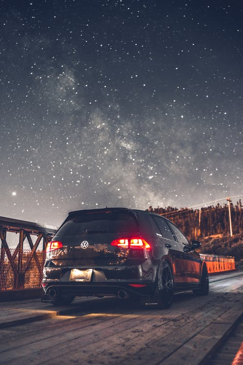 Contemporary crossover car parked on bridge against starry sky at winter night