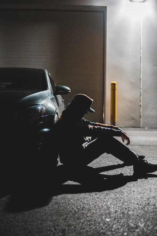 Anonymous sad man sitting on ground near parked contemporary car in evening