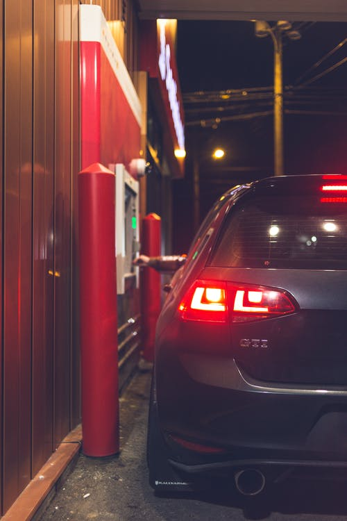 Unrecognizable person sitting in modern car and making purchases in drive through at night