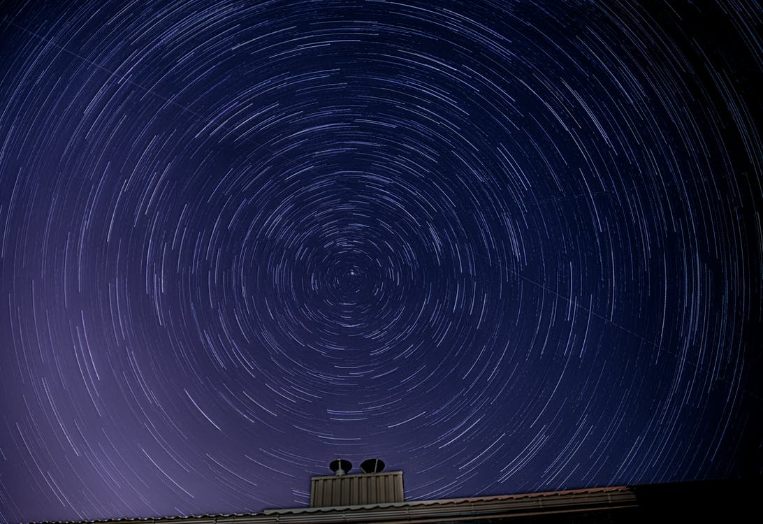 Stars in blue night sky over roof of building