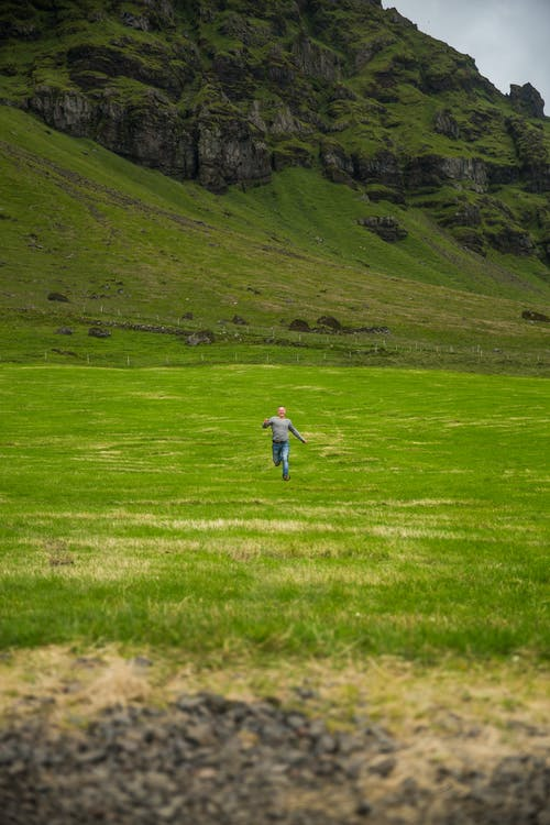 Faceless person running though meadow