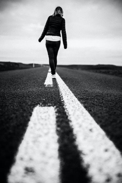 Faceless woman walking on spotted line on asphalt road