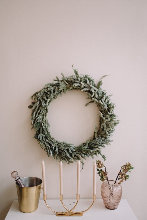 Festive wreath hanging on wall and decorative candles placed on table for Christmas holiday at home