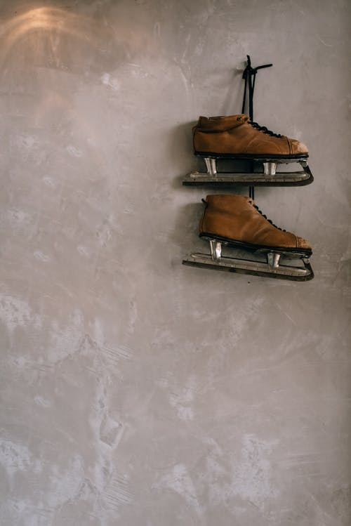 Retro skates hanging on wall in room