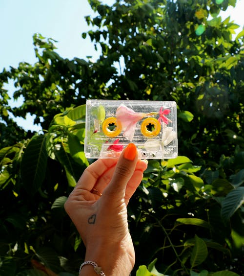 Person showing cassette with floral decoration