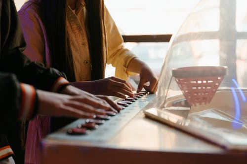 Woman in Yellow Coat Playing White and Black Keyboard