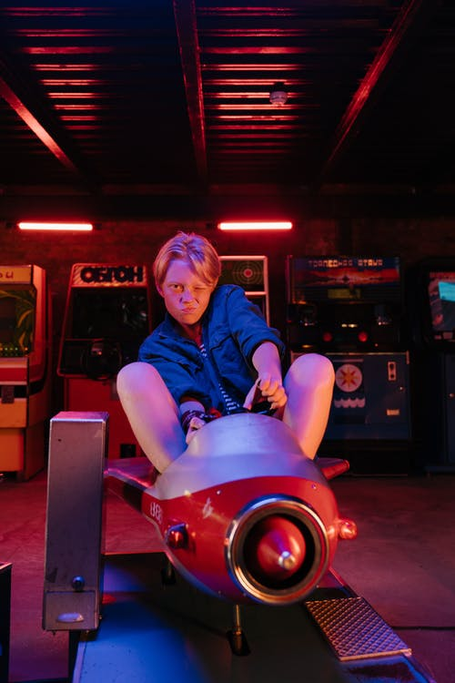 Woman in Blue Denim Jacket Riding Red Ride on Toy Car