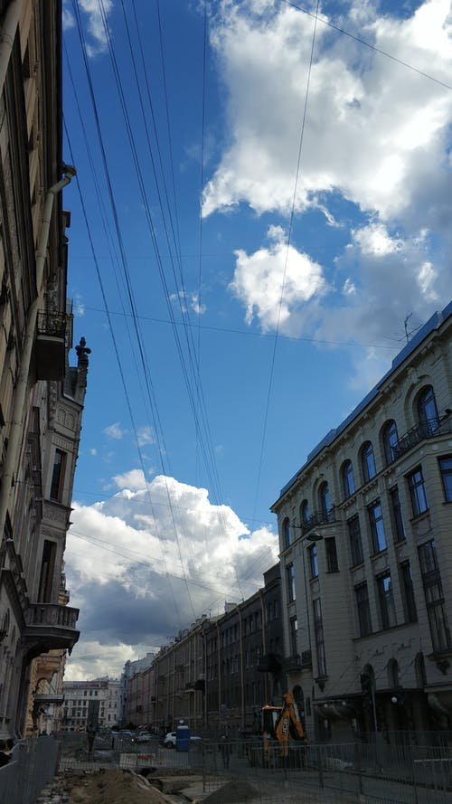 Low Angle Photography of Buildings Under Blue Sky and White Clouds