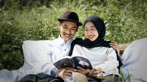 Man in White Dress Shirt Beside Woman in Black Hijab