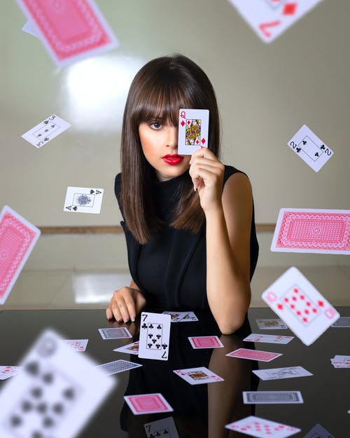 Woman covering face with playing card