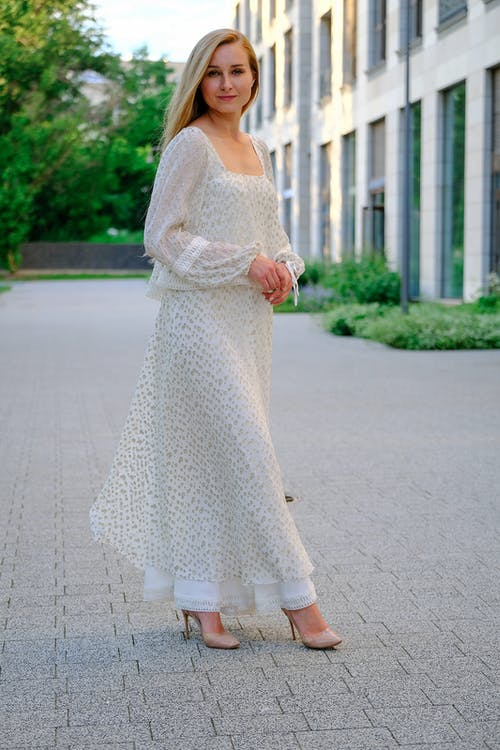 Full body of adult elegant female in maxi stylish dress standing on paved street and looking at camera