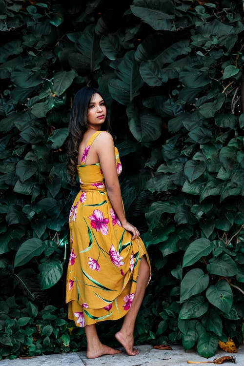 Woman in Yellow and Green Floral Sleeveless Dress Standing Beside Green Leaves