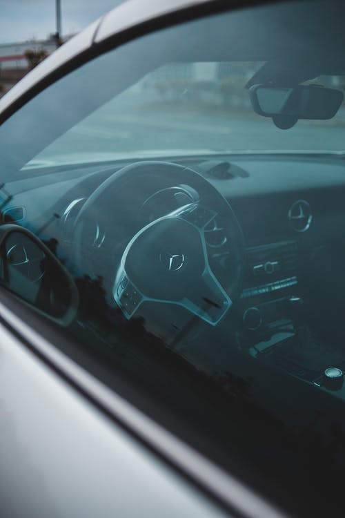 Through window of steering wheel and dashboard of modern stylish car parked on road on cloudy day