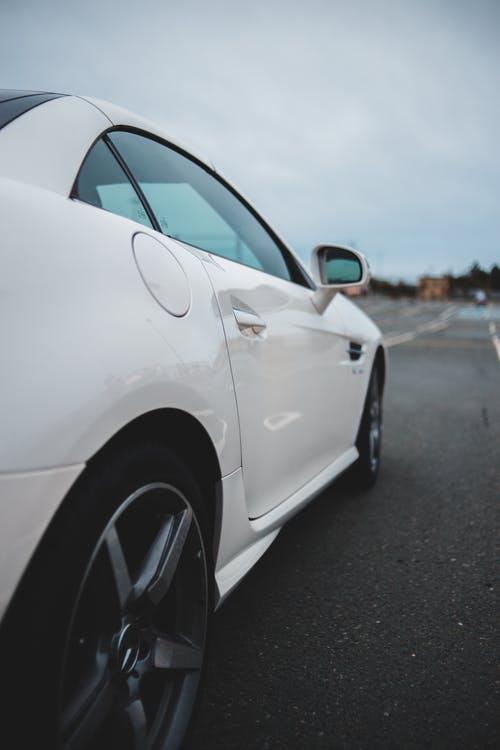 Door and tires of expensive modern white coupe car parked on asphalt road against cloudy sky