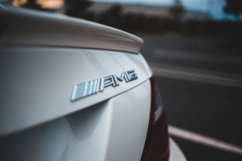 Closeup of chrome logotype on trunk of new shiny white modern car driving on asphalt road