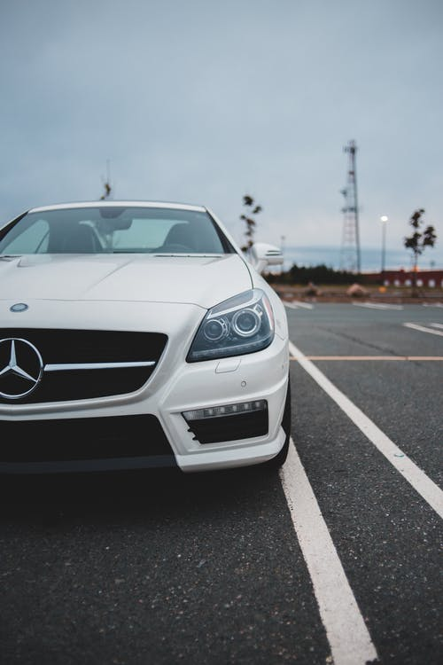 Bonnet of luxury white contemporary car parked on asphalt roadway against cloudy sky