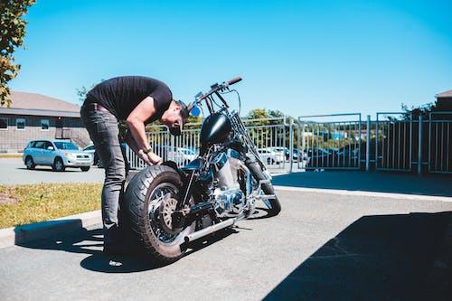 Man in Black Jacket and Black Pants Riding Black Cruiser Motorcycle