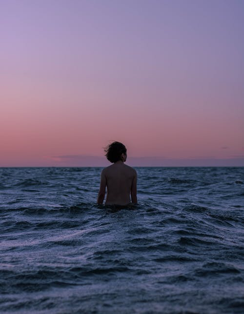 Anonymous traveler on wavy ocean admiring sky at sunset