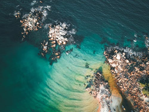 From above of picturesque scenery of wavy ocean with turquoise water and coastline with rough rocks