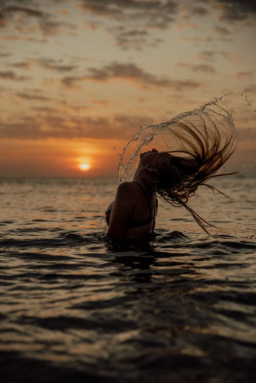 A Woman Flipping Her Hair in the Water during Sunset