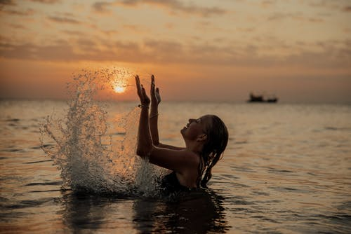 A Woman Swimming in the Sea during Sunset