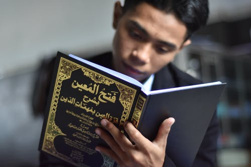 Close-Up Shot of a Man Reading a Book